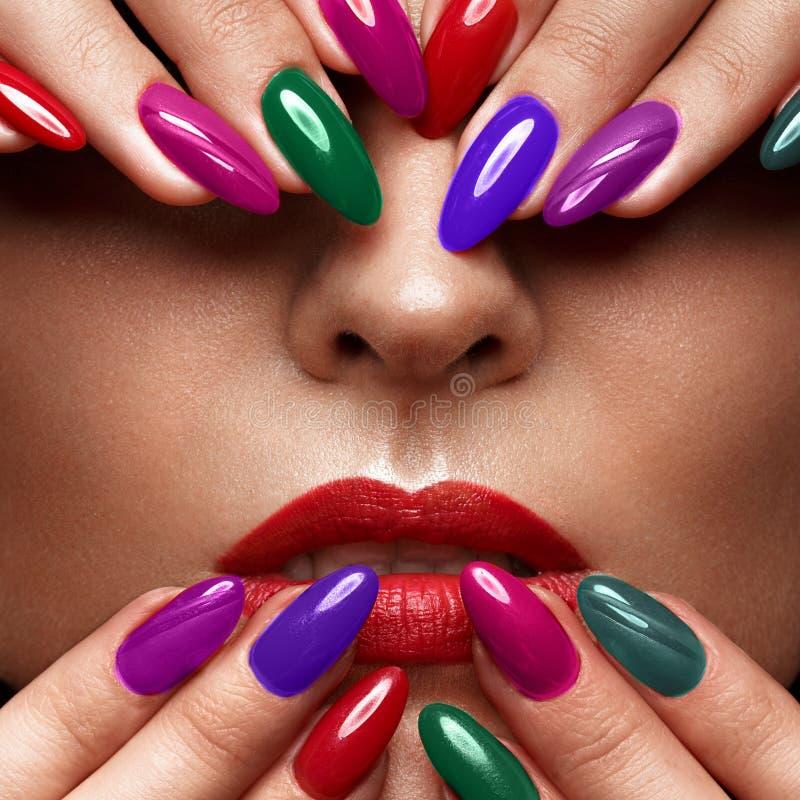 Mooi meisje met een klassieke samenstelling en multi-colored spijkers Manicureontwerp Het Gezicht van de schoonheid stock afbeeldingen