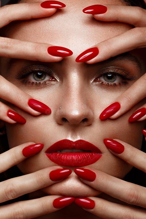 Mooi meisje met een klassieke samenstelling en rode spijkers Manicureontwerp Het Gezicht van de schoonheid stock foto's