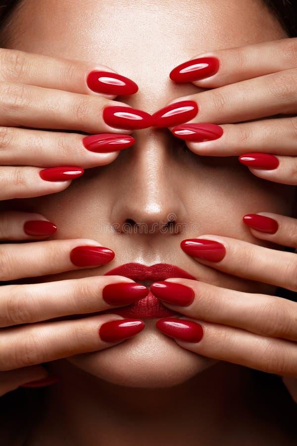 Mooi meisje met een klassieke samenstelling en rode spijkers Manicureontwerp Het Gezicht van de schoonheid royalty-vrije stock afbeeldingen