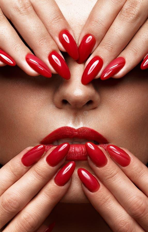 Mooi meisje met een klassieke samenstelling en rode spijkers Manicureontwerp Het Gezicht van de schoonheid royalty-vrije stock afbeelding