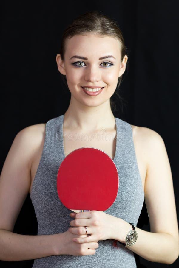 Mooi meisje met een racket voor pingpong op een zwarte achtergrond stock afbeelding
