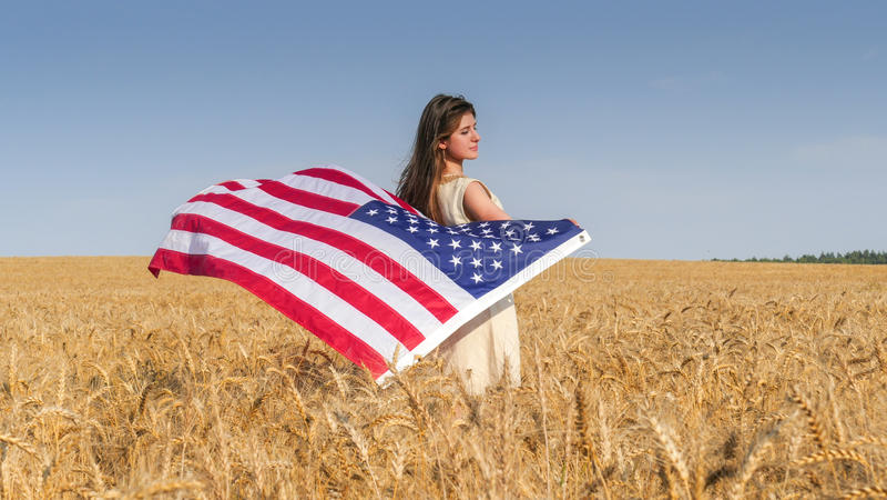 Mooi meisje met een vlag van de V.S. op het gebied stock fotografie