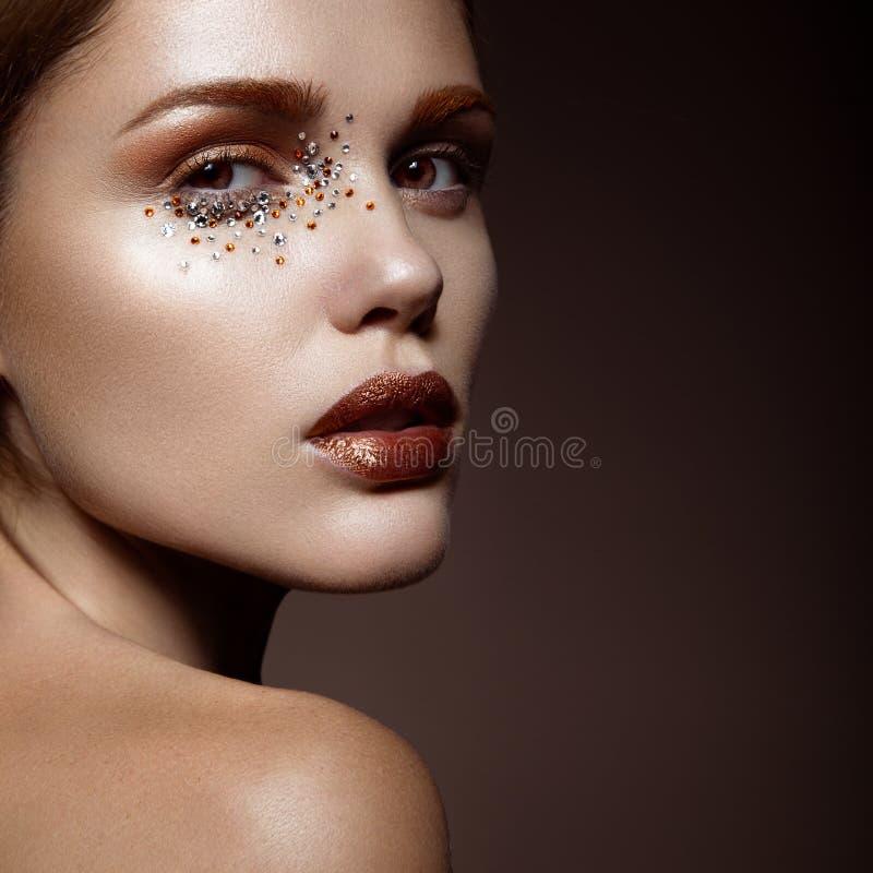 Mooi meisje met een zachte samenstelling en kristallen op het gezicht stock afbeelding