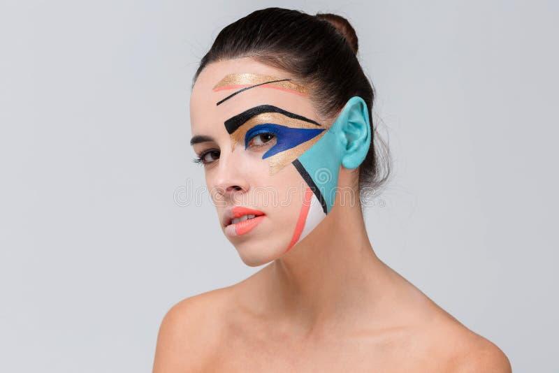 Mooi meisje, met gekleurde creatieve geometrische samenstelling op haar gezicht stock fotografie