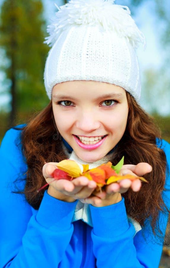 Mooi meisje met gele bladeren in haar handen stock fotografie
