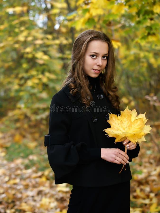 Mooi meisje met gele esdoornbladeren op handen royalty-vrije stock fotografie