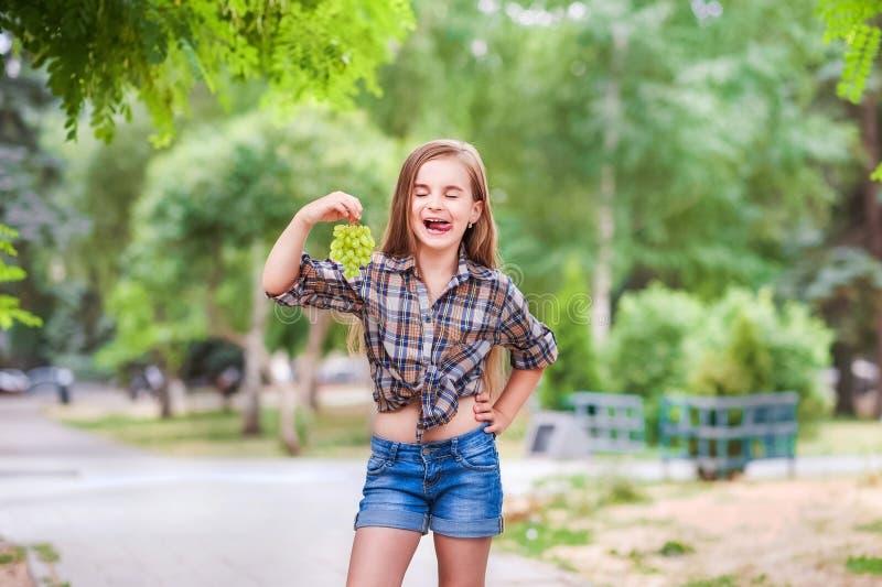 Mooi meisje met gesloten ogen die en witte lichte druiven glimlachen eten Een meisje in een plaidoverhemd en korte jeansborrels h royalty-vrije stock afbeeldingen