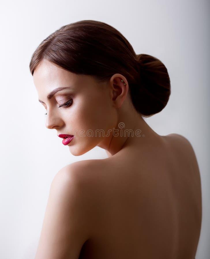 Mooi meisje met gesloten ogen en donkere haren, met schone huid, met naakte schouders Een model met samenstelling en roze lippen stock afbeeldingen