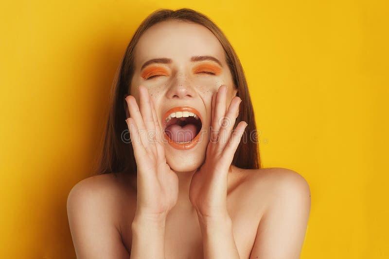 Mooi meisje met glanzend bruin recht lang haar Vrouw met oranje make-up met sproeten Meisje ogen het gesloten gillen royalty-vrije stock foto's