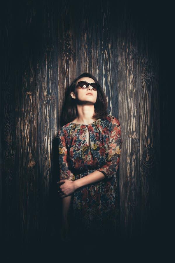 Mooi meisje met glazen op een houten achtergrond stock foto's