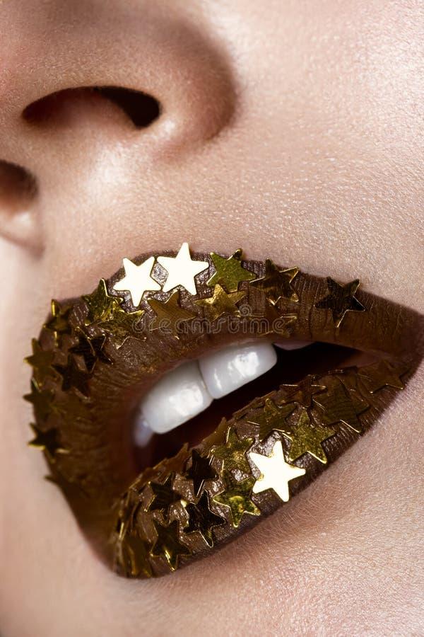 Mooi meisje met gouden glanzende sterren op haar lippen Het Gezicht van de schoonheid Sluit omhoog stock afbeelding