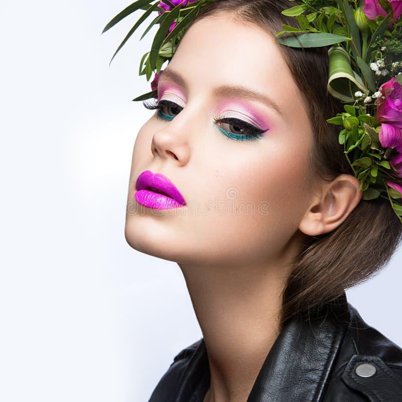 Mooi meisje met heel wat bloemen in hun haar en heldere roze samenstelling De lentebeeld Het Gezicht van de schoonheid stock afbeeldingen