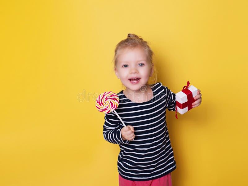 Mooi meisje met helder lollysuikergoed en gift op gele backgr royalty-vrije stock afbeeldingen