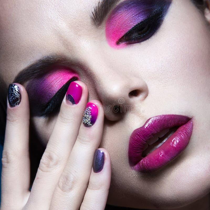 Mooi meisje met heldere creatieve maniermake-up en kleurrijk nagellak Het ontwerp van de kunstschoonheid stock fotografie