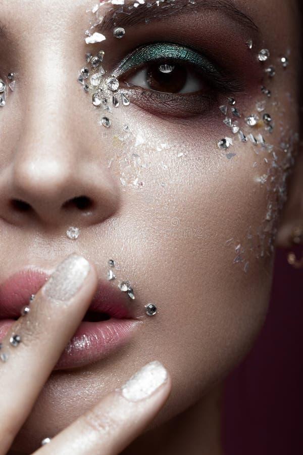 Mooi meisje met heldere kleurenmake-up en kristallen op het gezicht De gelukkige jonge zakken van de meisjesholding op een witte  royalty-vrije stock foto's