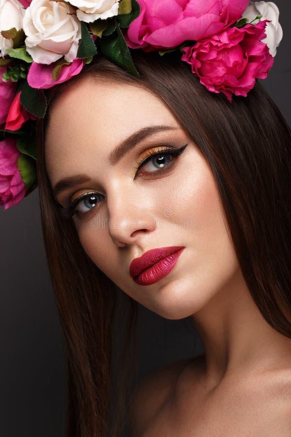 Mooi meisje met heldere samenstelling en bloemen op haar hoofd Het Gezicht van de schoonheid stock afbeeldingen