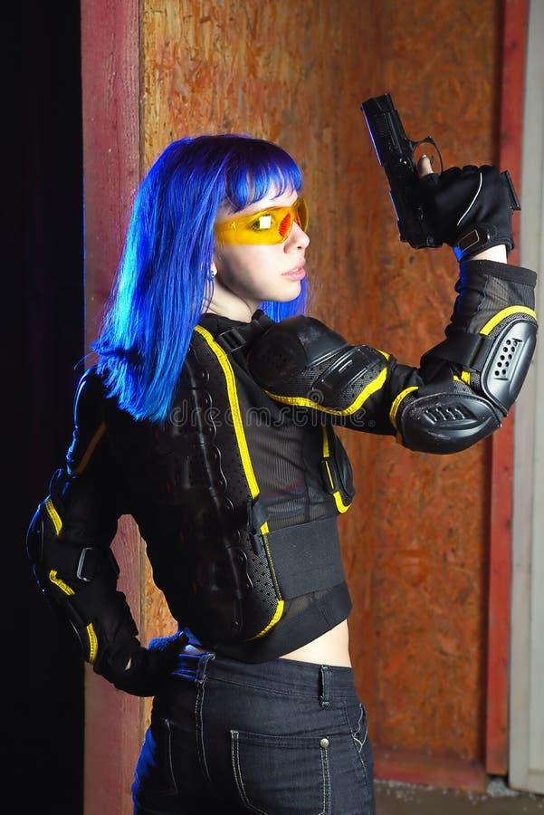Mooi meisje met het blauwe kanon van de haarholding op de achtergrond van de strikeballplaats royalty-vrije stock afbeelding