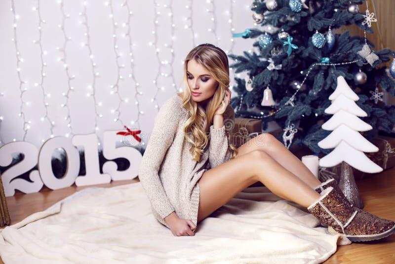 Mooi meisje met het blonde haar stellen naast een Kerstboom stock fotografie