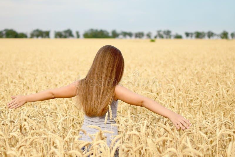 Mooi meisje met het lange erfgenaam lopen door gouden tarwegebied Concept zuiverheid, de groei, geluk stock fotografie