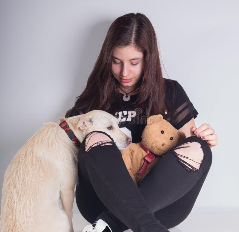 Mooi meisje met het teddybear en droevige kijken hond stock afbeelding