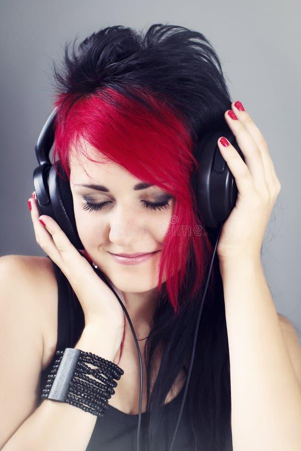 Mooi meisje met hoofdtelefoons genieten die aan de muziek luisteren royalty-vrije stock foto
