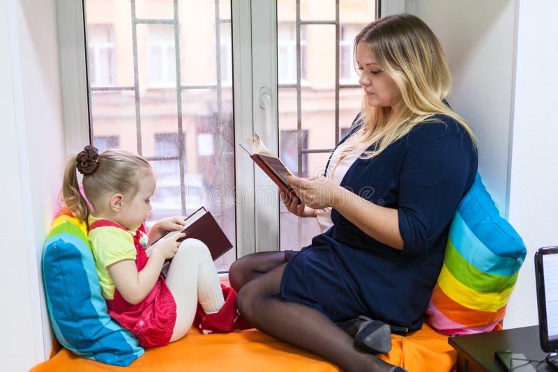 Mooi meisje met jonge moeder gelezen boeken op venstervensterbank stock foto