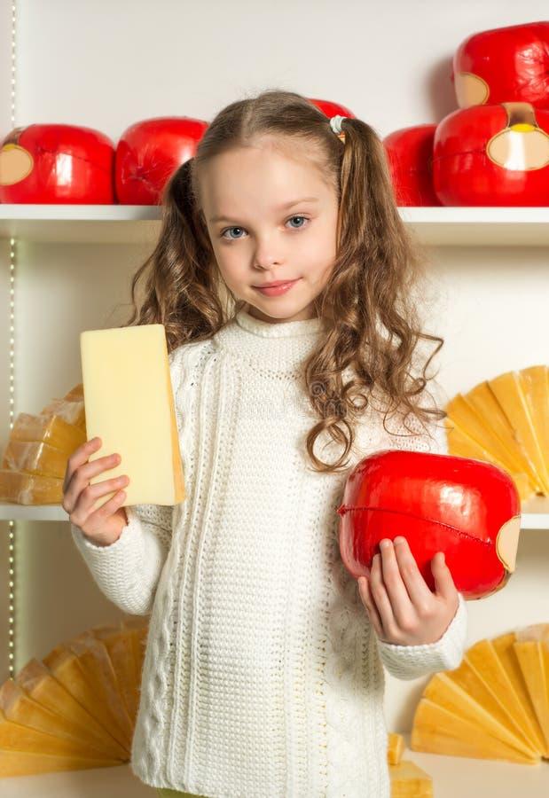 Mooi meisje met kaas in de handenvoorzijde van planken stock foto