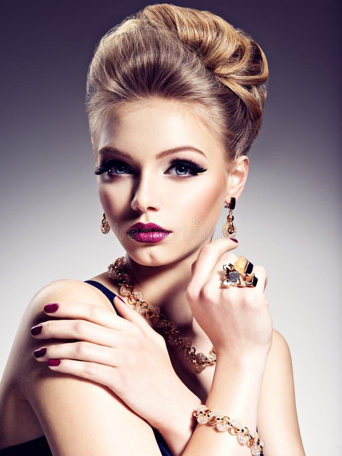 Mooi meisje met mooi kapsel en gouden juwelen, helder m stock foto's