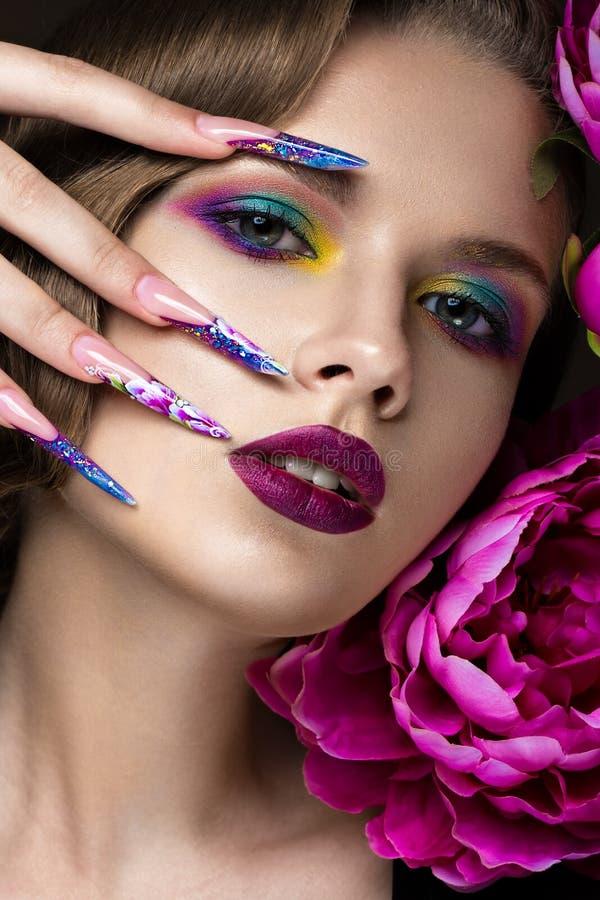 Mooi meisje met kleurrijke samenstelling, bloemen, retro kapsel en lange spijkers Manicureontwerp De schoonheid van het gezicht royalty-vrije stock foto's