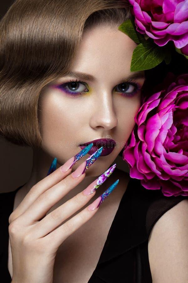 Mooi meisje met kleurrijke samenstelling, bloemen, retro kapsel en lange spijkers Manicureontwerp De schoonheid van het gezicht stock foto's