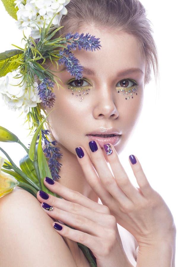 Mooi meisje met kunstsamenstelling, bloemen, en de manicure van ontwerpspijkers Het Gezicht van de schoonheid stock fotografie