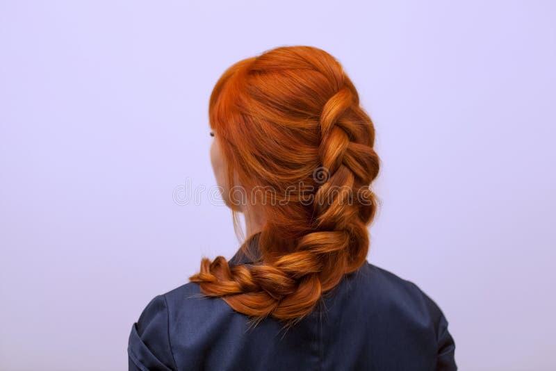 Mooi meisje met lang rood die haar, met een Franse vlecht, in een schoonheidssalon wordt gevlecht stock fotografie