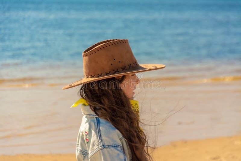 Mooi meisje met lang zwart haar in een cowboyhoed op het strand op een zonnige dag royalty-vrije stock fotografie