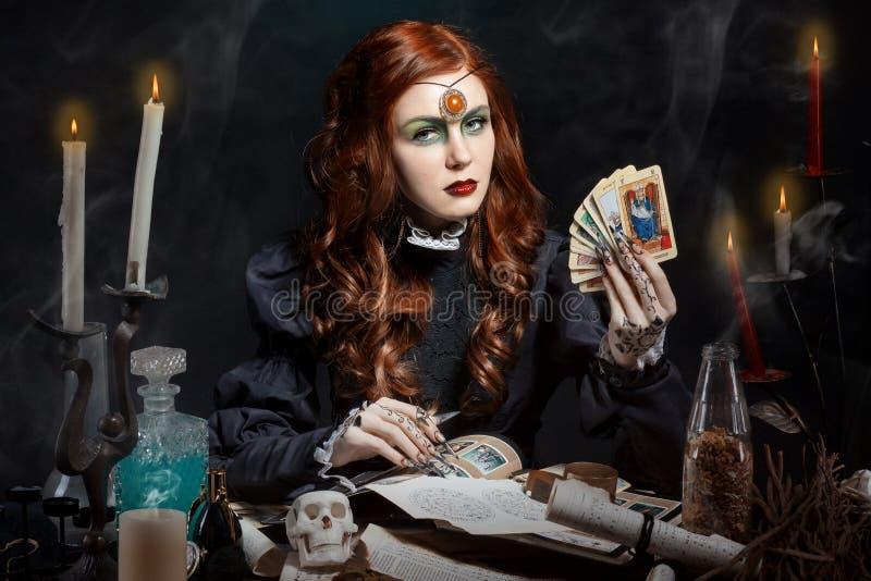 Mooi meisje met lange haarwijze in het beeld van de heks met de Tarotkaarten in zijn handen, zwarte lange valse spijkers met held stock afbeelding