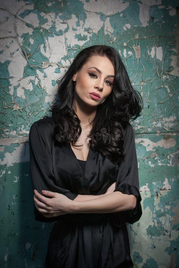 Mooi meisje met make-up het stellen tegen oude muur met schil groene verf Mooie brunette in zwarte Aantrekkelijke donkere haarvro stock foto