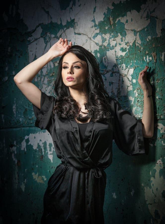 Mooi meisje met make-up het stellen tegen oude muur met schil groene verf Mooie brunette in zwarte Aantrekkelijke donkere haarvro royalty-vrije stock afbeelding