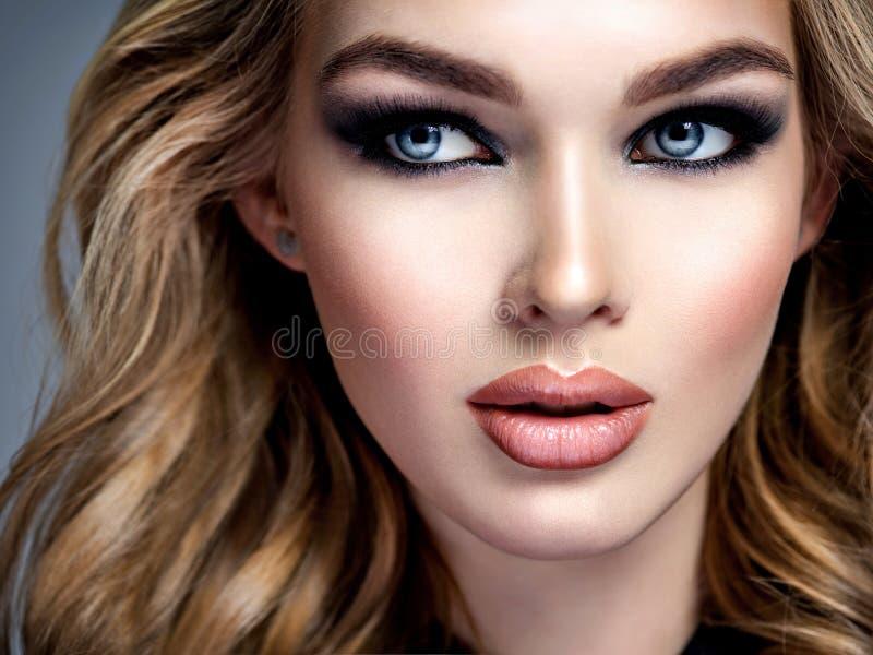 mooi meisje met make-up in stijl rokerig oog stock foto's