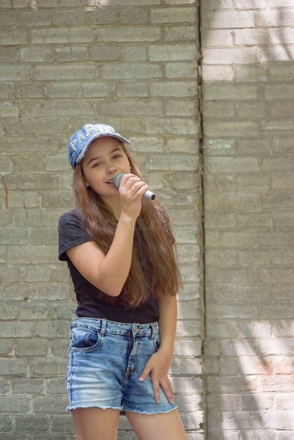 Mooi meisje met microfoon op bakstenen muurachtergrond royalty-vrije stock foto's