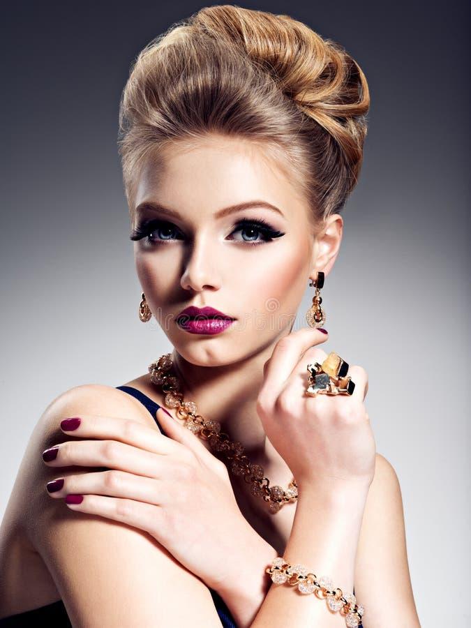Mooi meisje met mooi kapsel en gouden juwelen, helder m royalty-vrije stock afbeeldingen