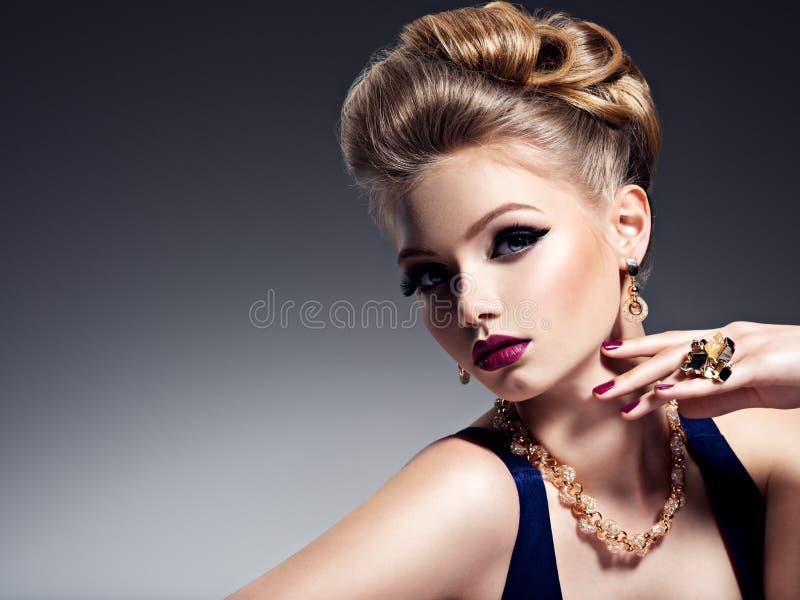 Mooi meisje met mooi kapsel en gouden juwelen, helder m royalty-vrije stock fotografie