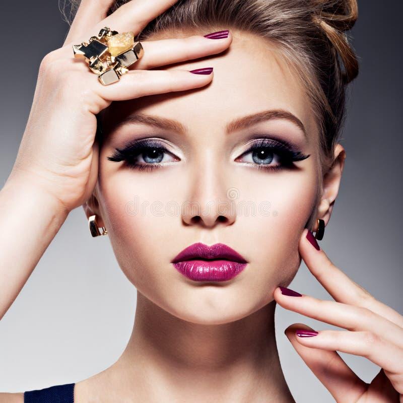 Mooi meisje met mooie gezichts heldere samenstelling en gouden juwelen stock foto's