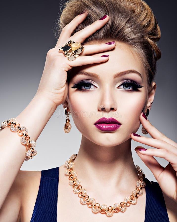Mooi meisje met mooie gezichts heldere samenstelling en gouden juwelen stock foto