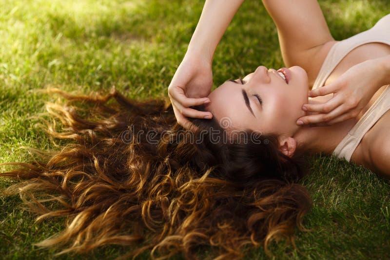 Mooi meisje met natuurlijke zuivere huid die en, op het gazon in openlucht liggen ontspannen stock afbeeldingen
