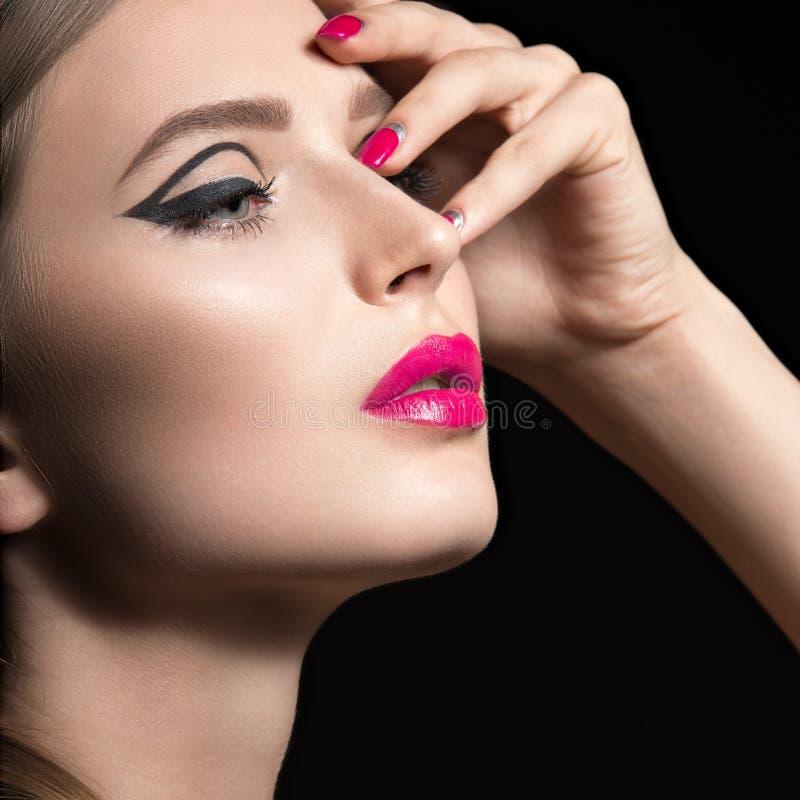 Mooi meisje met ongebruikelijke zwarte pijlen op ogen en roze lippen en spijkers Het Gezicht van de schoonheid stock foto
