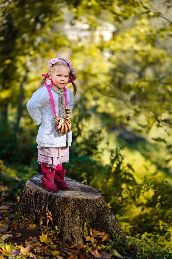 Mooi meisje met ongezuurde broodjes in de herfstpark stock foto's