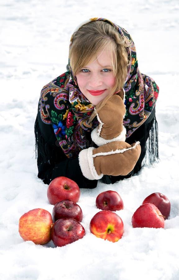 Mooi meisje met rode appelen op sneeuw stock afbeelding