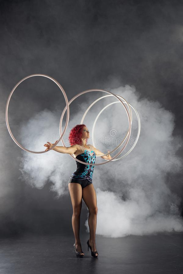 Mooi meisje met rode de kunstenaars spinnende hoepels van het haarcircus op handen stock foto