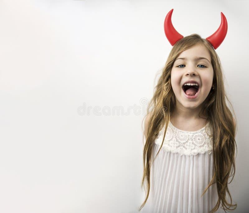 Mooi meisje met rode hoornen die en aan camera stellen glimlachen royalty-vrije stock foto's