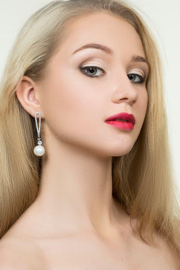 Mooi meisje met rode lippen en oorringen Manier stock foto