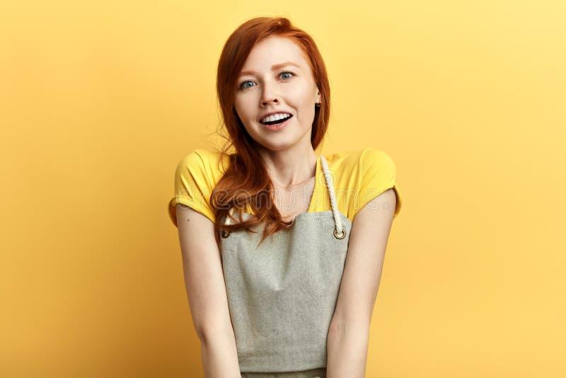 Mooi meisje met rood haar en toothy glimlach expesses positieve emotie royalty-vrije stock afbeelding